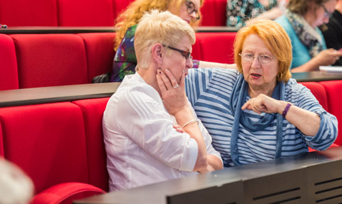 Two women in discussion in the audience of a lecture theatre