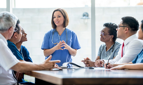 Medical professionals in discussion around a table in a meeting room
